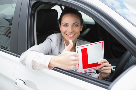 female driver: Female driver giving thumbs up while holding her L sign in her car Stock Photo