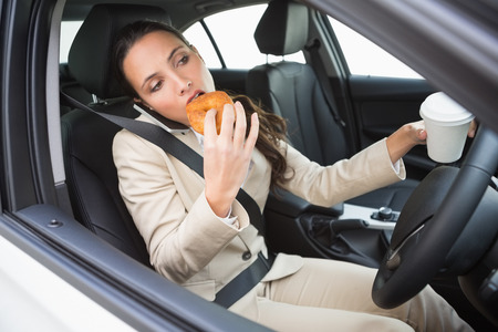 Businesswoman having coffee and doughnut on the phone in her car