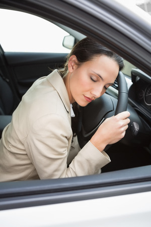 Businesswoman sleeping on the wheel in her car Stock Photo