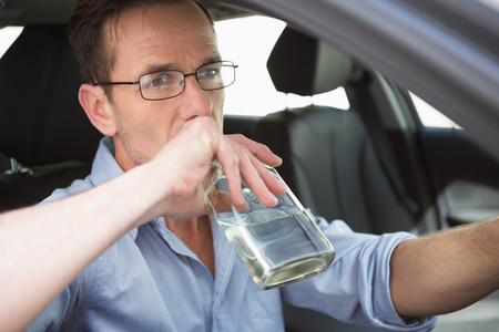 life threatening: Man drinking wine while driving in his car