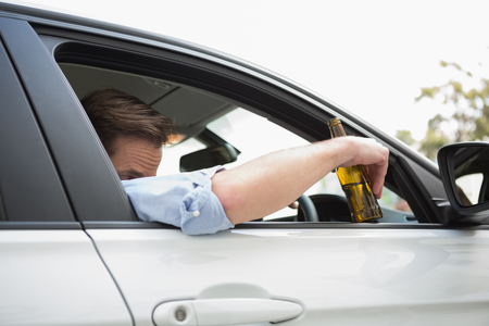 slumped: Man drinking beer while driving in his car