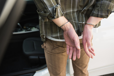 restraining device: Close up of handcuffed man in a car park