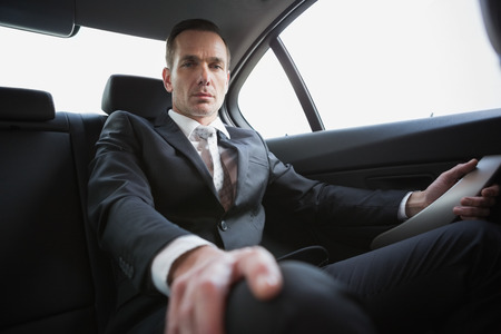 unsmiling: Unsmiling businessman sitting in the back seat in his car