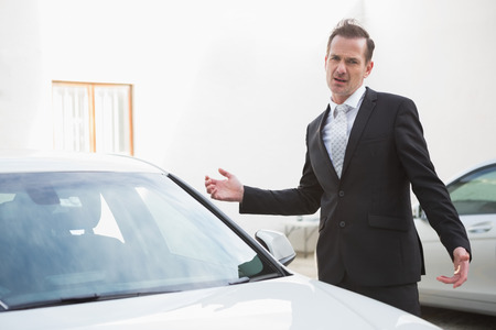 breaking down: Businessman looking his car engine after breaking down in a car park