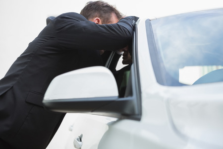 wistfulness: Businessman looking inside the car in a car park Stock Photo