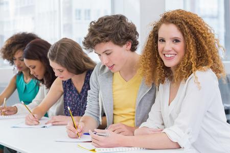 persona escribiendo: Estudiantes de moda que toma notas en clase en la universidad