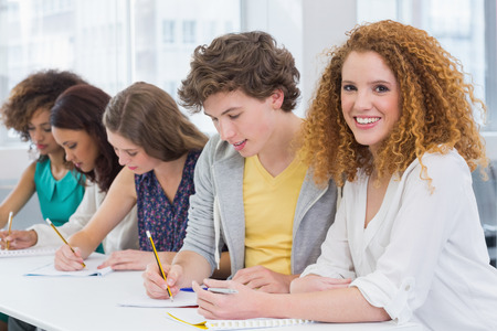 persona escribiendo: Fashion students taking notes in class at the college