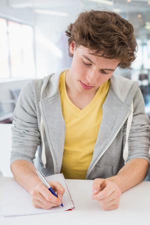 hombre escribiendo: Estudiante que toma notas en clase en la universidad