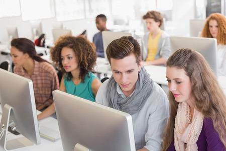 usando computadora: Los estudiantes que trabajan en la sala de ordenadores en el colegio Foto de archivo