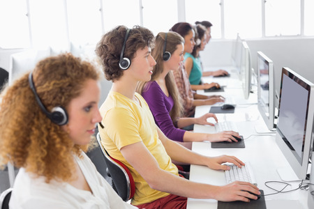 girl with headphones: Students working in computer room at the college