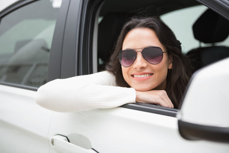 window shades: Woman wearing sunglasses smiling at camera in her car