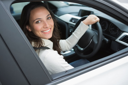 drivers seat: Smiling woman in the drivers seat in her car