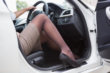 business woman legs: Businesswoman getting out the front door in her car