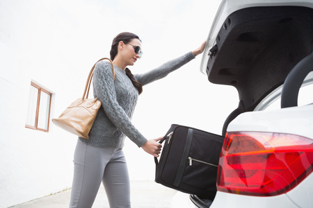 car trunk: Woman pulling out a baggage of her car trunk in a car park Stock Photo