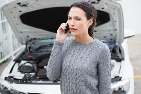 broken down: Annoyed woman on the phone beside her broken down car in a car park