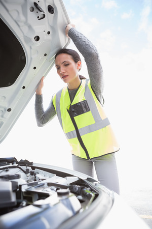 empty tank: Upset woman checking her car engine in a car park Stock Photo