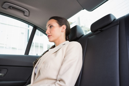 back seat: Unsmiling businesswoman sitting in the back seat in her car Stock Photo