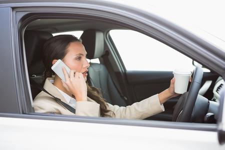 mujer tomando cafe: Mujer de tomar café en el teléfono mientras se conduce en su coche Foto de archivo