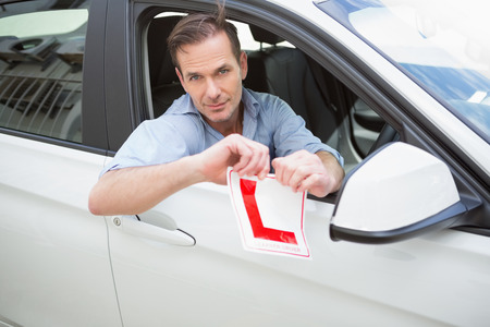 l plate: Smiling male driver tearing up his L sign in his car