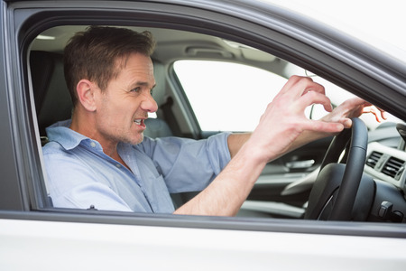 road rage: Handsome man experiencing road rage in his car Stock Photo