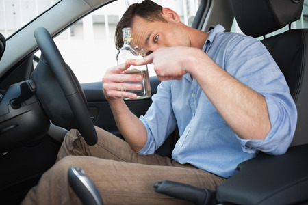 life threatening: Man showing an empty bottle of vodka in his car