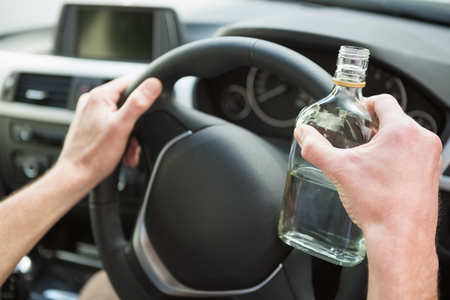 life threatening: Close up of a man holding a bottle of vodka in his car Stock Photo