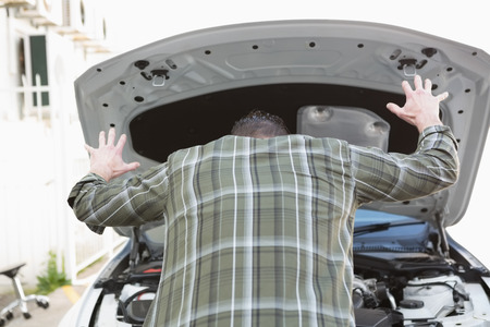 breaking down: Angry man checking his car engine after breaking down in a car park