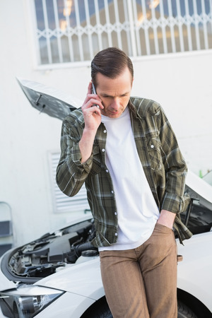 breaking down: Unsmiling man calling for assistance after breaking down in a car park