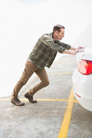 broken down: Man pushing his broken down car in a car park