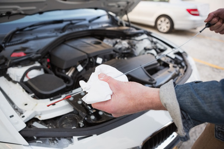 oil park: Close up of man checking car engine oil in a car park Stock Photo