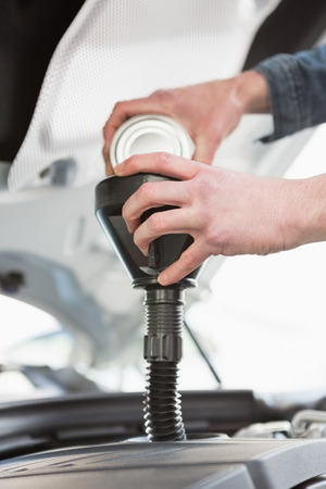 engine bonnet: Man pouring oil into engine of his car