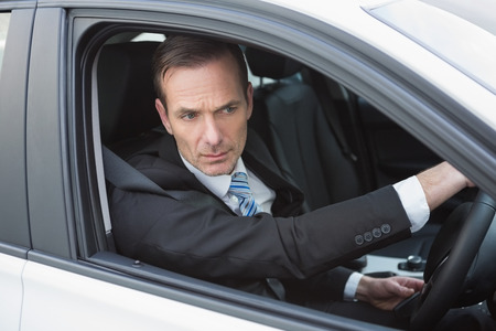 unsmiling: Unsmiling businessman in the drivers seat in his car