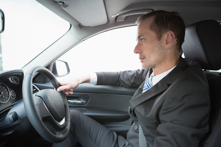 drivers seat: Handsome businessman in the drivers seat in his car Stock Photo