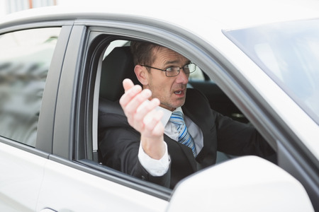 rage: Handsome businessman experiencing road rage in his car Stock Photo