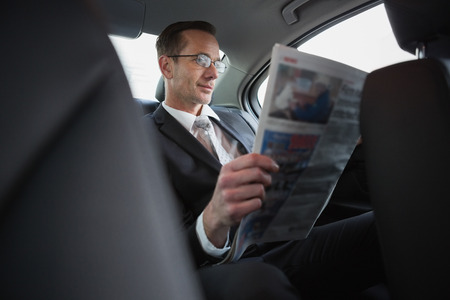 newspaper reading: Focused businessman reading the newspaper in his car Stock Photo