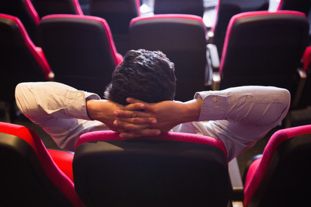 hands on head: Young man with hands head watching a film at the cinema