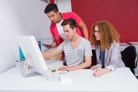 Concentrated students using tablet and computer at the college photo