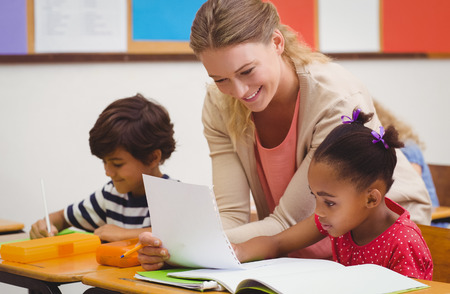 early childhood: Pretty teacher helping pupil in classroom at the elementary school Stock Photo