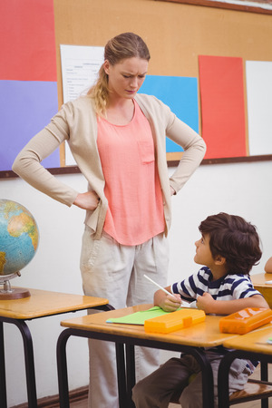 Angry teacher looking pupil with hands on hips at the elementary school Imagens