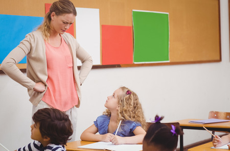 anger kid: Angry teacher looking pupil with hands on hips at the elementary school Stock Photo