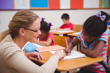asian teacher: Cute pupil getting help from teacher in classroom at the elementary school