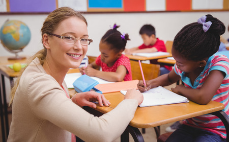 teaching adult: Cute pupils writing at desk in classroom at the elementary school Stock Photo