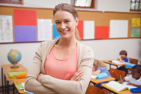 female pose: Pretty teacher smiling at camera with arms crossed at the elementary school Stock Photo