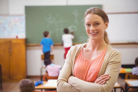 Mooie leraar glimlachen op de camera aan de achterkant van de klas op de lagere school Stockfoto