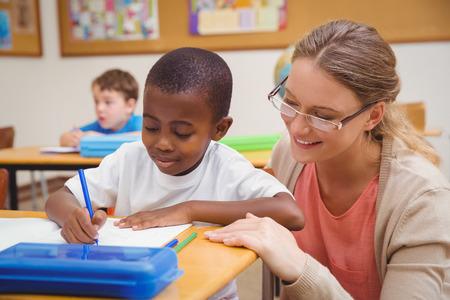 niño escuela: Pretty profesor de ayudar a los alumnos en el aula en la escuela primaria Foto de archivo