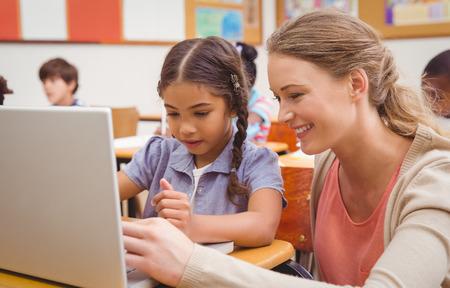profesor alumno: Lindo alumno usando la computadora con el maestro en la escuela primaria