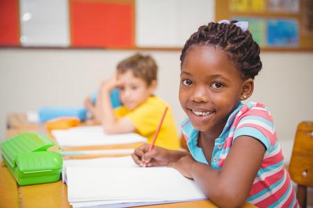 Roztomilý žáci kreslení u svého stolu jeden s úsměvem na kameru na základní škole