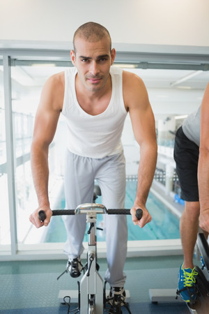 man working out: Portrait of a handsome young man working out on exercise bike at the gym