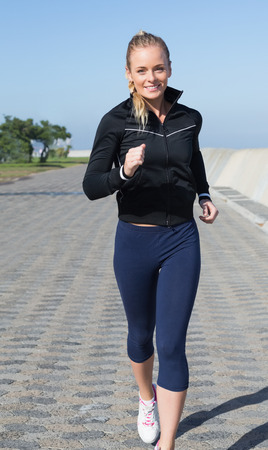 woman with camera: Fit blonde jogging on the pier on a sunny day Stock Photo