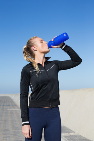out of water: Fit blonde drinking water on the pier on a sunny day Stock Photo